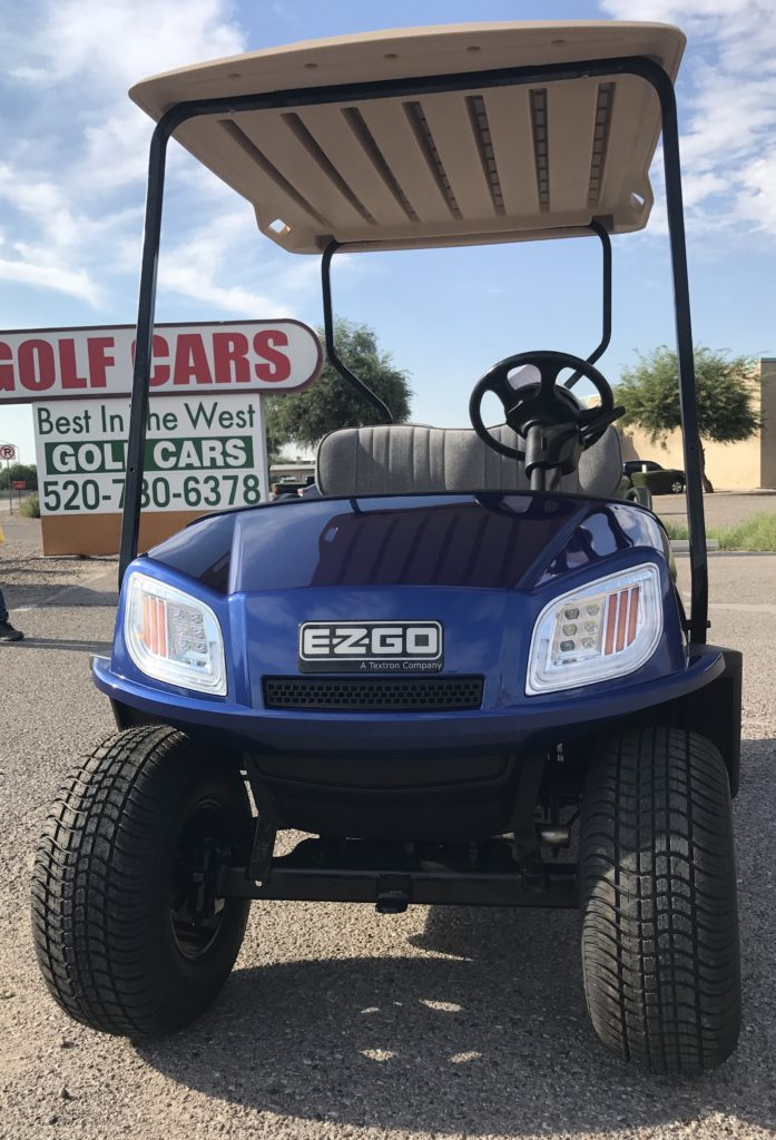 blue golf car in front of sign